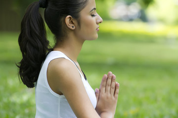 Young woman with hands in prayer position