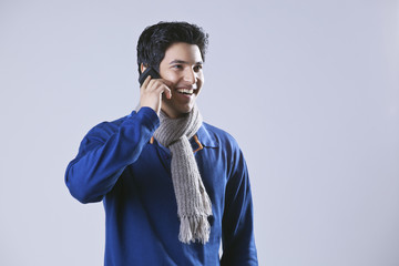 Young man having conversation on mobile phone and looking away