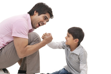 Young man arm wrestling with his son over white background