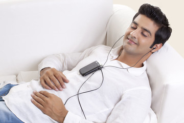 Relaxed young man listening music through cell phone