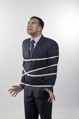 Businessman tied up with rope