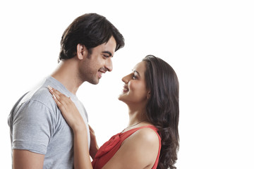 Side view of loving couple looking at each other against white background