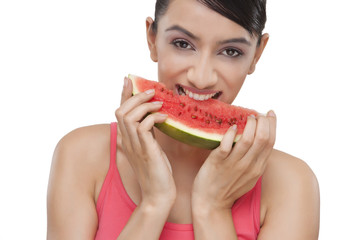 Close-up portrait of smiling young woman with a slice of watermelon over white background