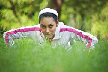 Portrait of young woman doing push-up on grass