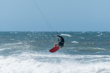 Kiteboarder enjoy surfing on a sunny day.
