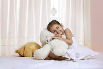 Portrait of smiling girl hugging teddy bear