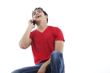 Cheerful young man laughing on the phone over white background