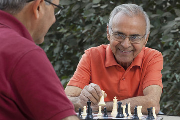 Senior man smiling at friend while holding chess piece