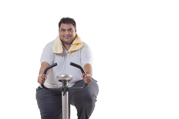 Portrait of an obese man exercising over white background