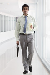 Businessman with bag and coffee cup walking in office corridor