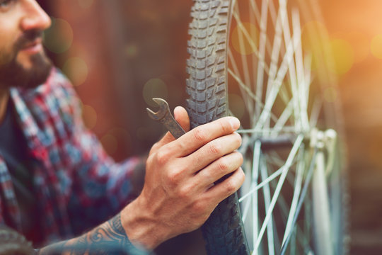 man repairing bike with wrench