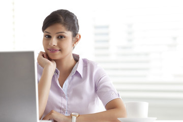 Relaxed young businesswoman sitting at her desk