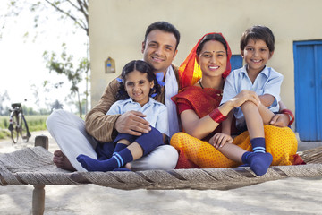 Portrait of happy rural Indian family sitting on cot