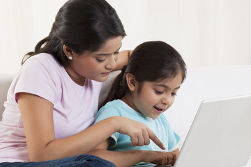 Mother assisting daughter using laptop