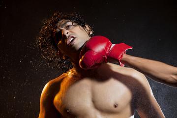 Handsome male boxer striking opponent