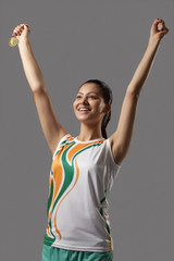 Happy young woman holding medal while celebrating victory isolated over white background