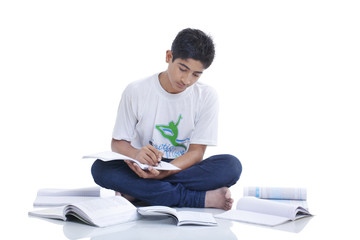 Teenage boy sitting on floor cross-legged studying against white background