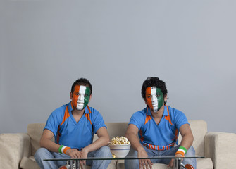Male friends with face painted in Indian tricolor sitting on sofa with bowl of popcorn on table at home