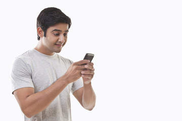 Young man reading text message and smiling