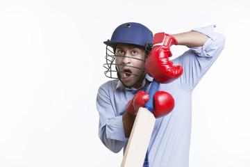 Cricketer holding bat over white background