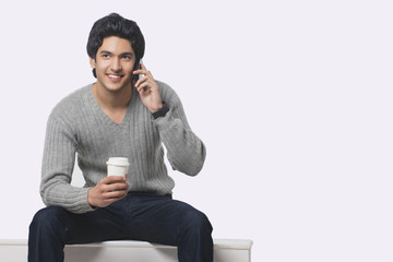 Young man talking on cell phone while holding disposable cup