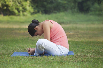 Young woman doing stretching exercise in park