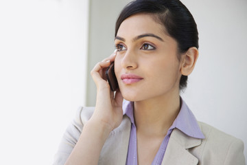 Beautiful businesswoman smiling while using mobile phone in office