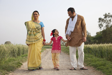 Full length of an Indian family walking on a rural road