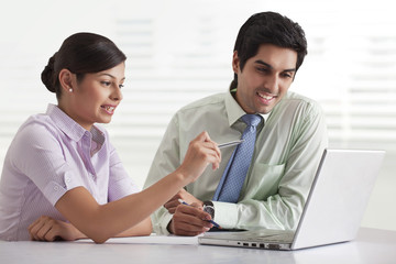 Two businesspeople preparing presentation while using laptop