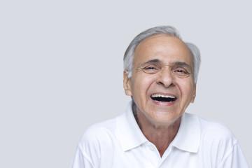 Senior man laughing over white background