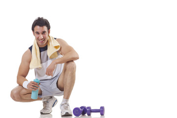 Portrait of a young man sitting next to a pair of dumbbell over white background