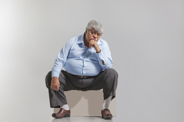 Obese old man feeling sad