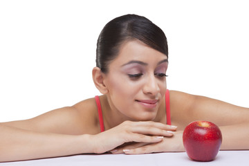 Close-up of beautiful young woman staring at fully ripped apple over white background