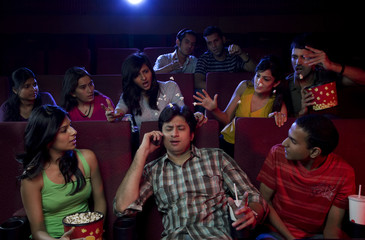 Man talking on a mobile phone in a cinema hall