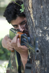 Young soldier aiming with rifle while standing behind tree