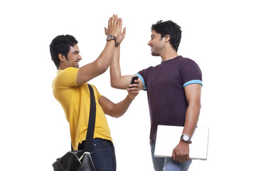 Two young men giving high-five