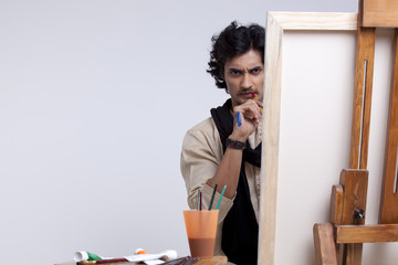 Portrait of young artist contemplating against colored background