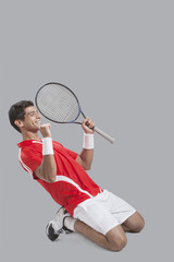 Happy male tennis player celebrating success over gray background