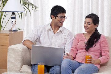 Young couple sitting on sofa using laptop with juice