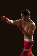 Side view of young male boxer punching isolated over black background