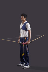 Full length of young male archer with bow and arrow over gray background