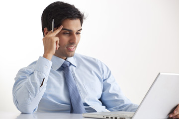 Smiling young businessman using laptop