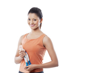 Portrait of a happy young woman holding jump rope over white background