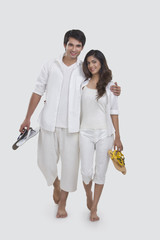 Portrait of loving young couple holding slippers while walking over white background