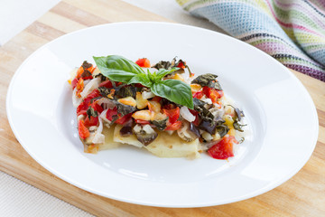 Oven roasted vegetables with cheese on white plate