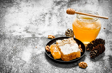 Wall Mural - Fresh honey in a jar and honeycomb with nuts.