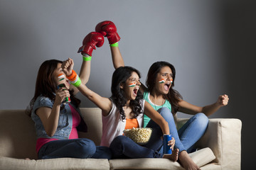Enthusiastic young female friends screaming out while watching boxing match together at home