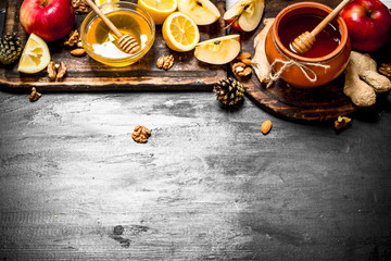 Wall Mural - Honey background. Honey in pot with apples, lemon , ginger and nuts.