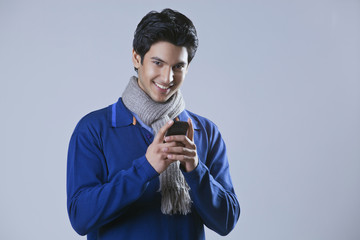 Portrait of young man holding mobile phone