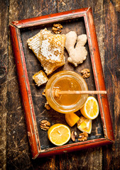 Wall Mural - Honey background . Fresh honey with lemon and ginger in an old tray.